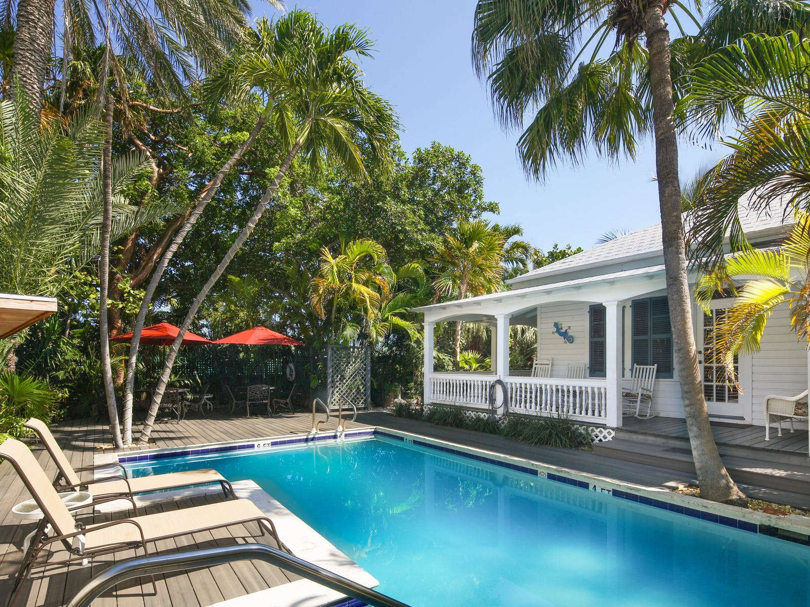 Outdoor pool with lounge chairs and palm trees near a white vacation home in Key West, FL.