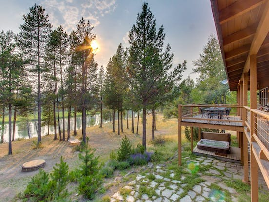 Sunriver riverfront vacation rental with hot tub and hammock surrounded by tall pine trees