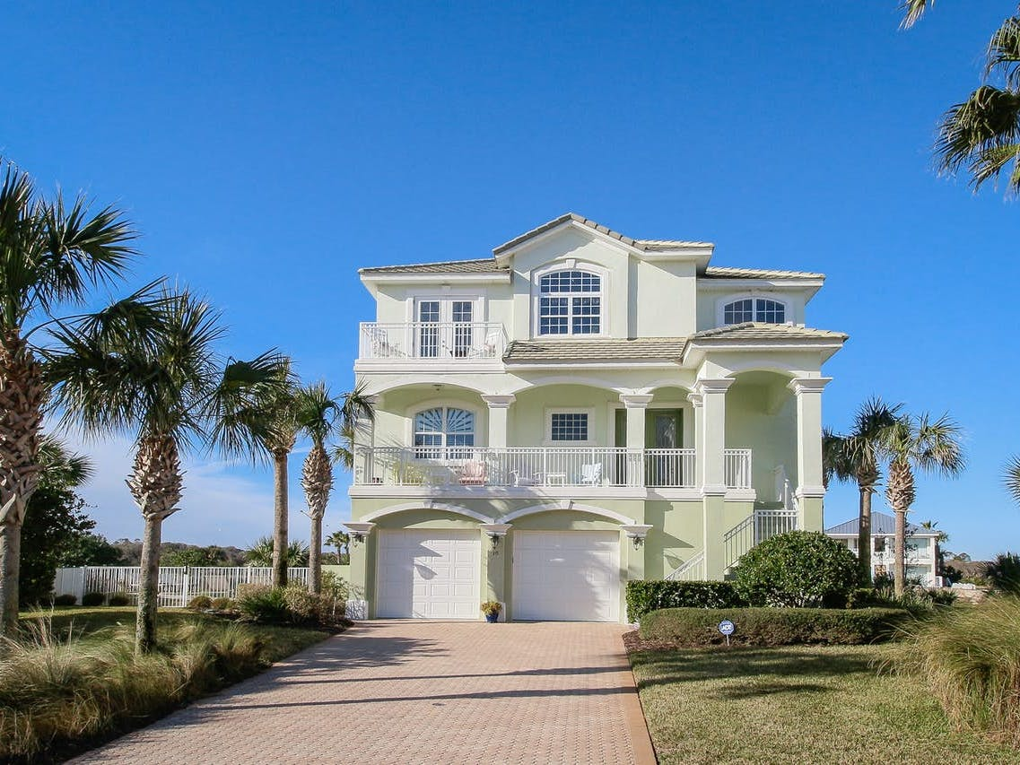 Pastel green Florida beach home with two car garage