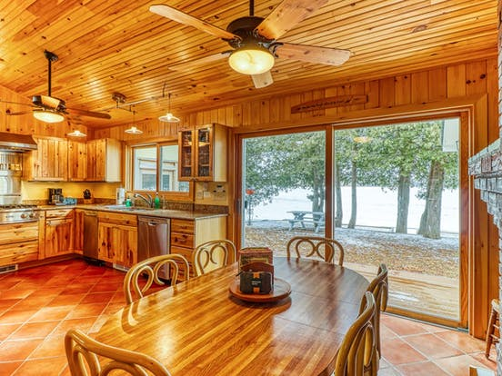 interior of North Hero, VT vacation rental with wood paneled kitchen and dining room table
