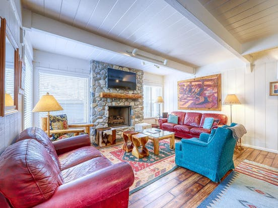 stone fireplace with colorful couches and decor inside Sun Valley vacation rental