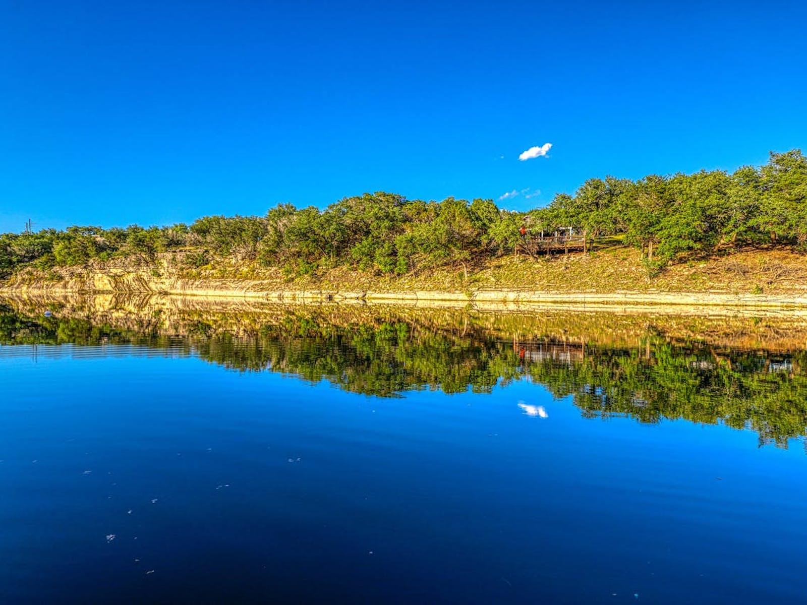 one cloud in blue ski over lake travis