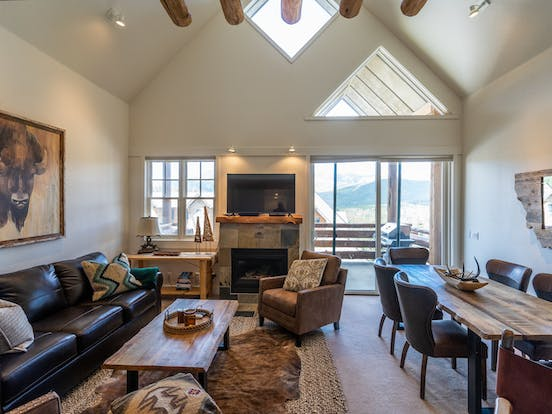 living room of big sky, mt vacation rental with fireplace and balcony with epic views