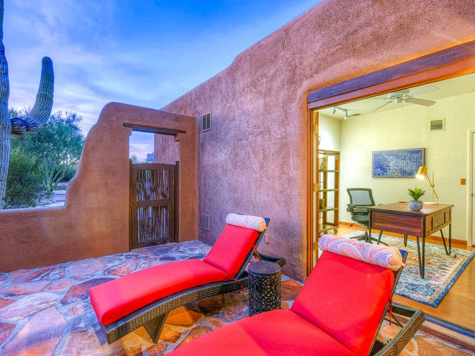 large cactus near vacation rental patio with red lounge chairs