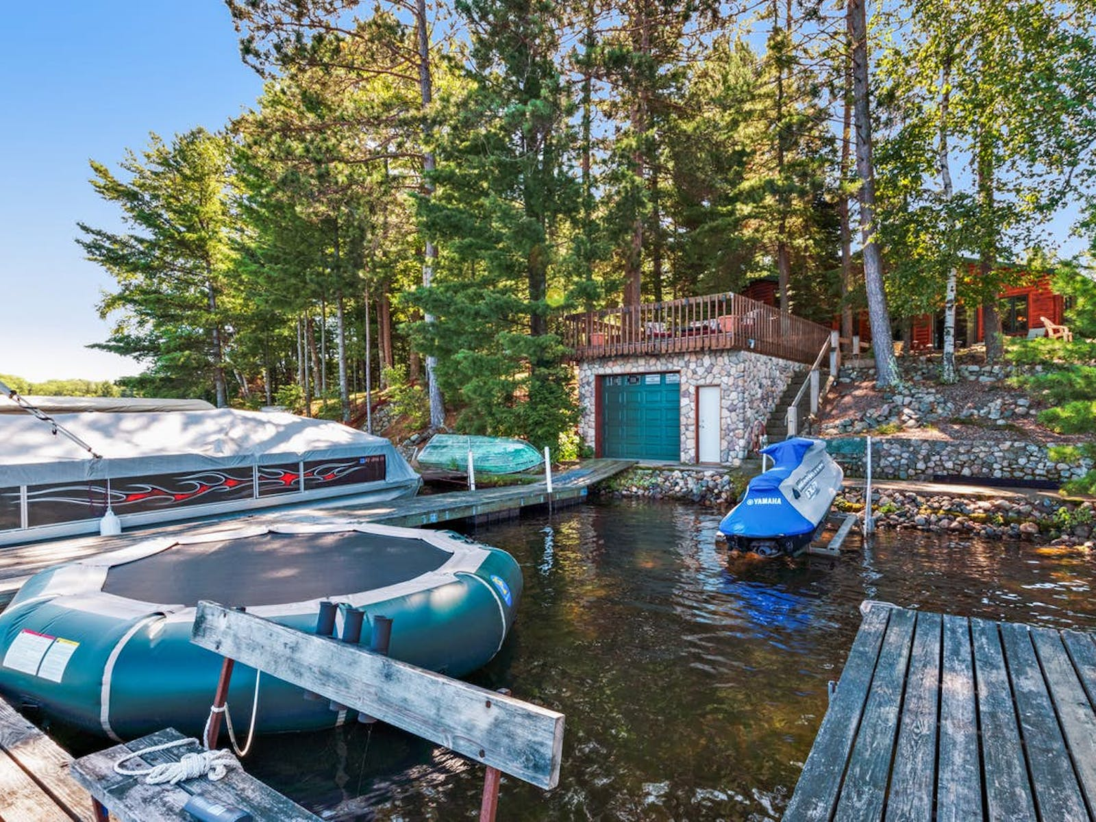 vacation rental right on Lake Tomahawk with water trampoline, boat and dock