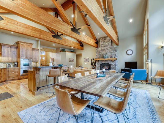 large open layout of sunriver, or vacation home with exposed rafters and large fireplace
