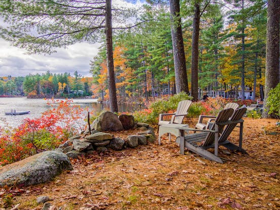 Vacation rental chairs around a fire pit overlooking a body of water