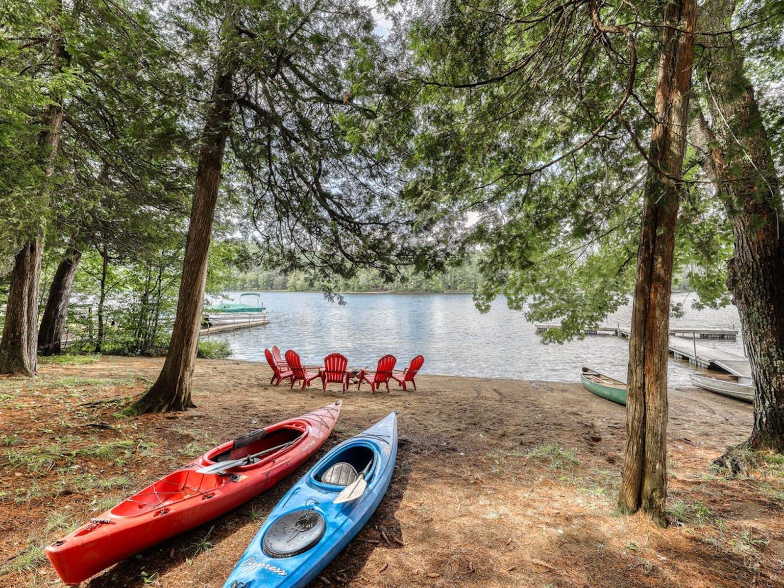 Two kayaks sit near waters edge in The Adirondacks