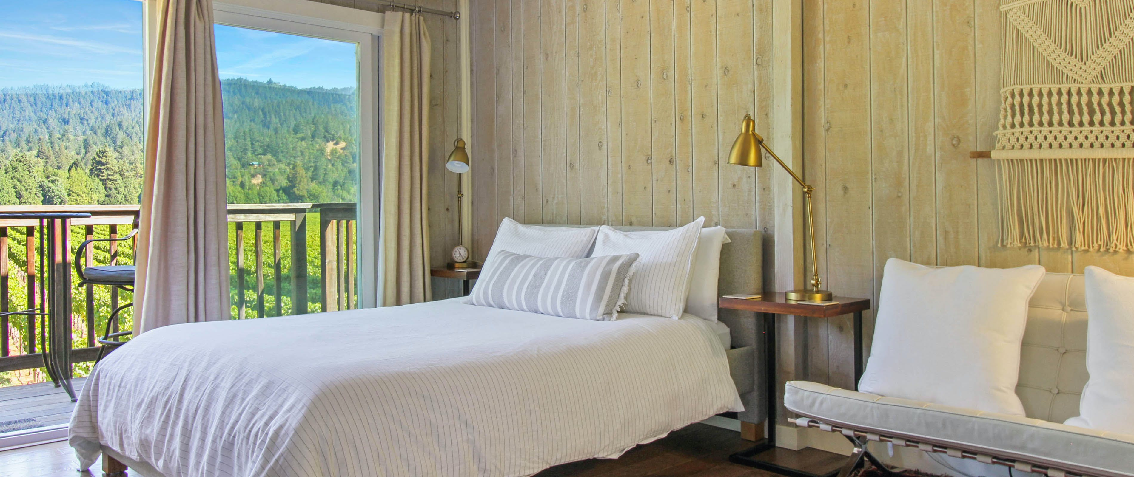 Inside a Guerneville, CA vacation rental bedroom with wooden wall panels and balcony overlooking a forest.