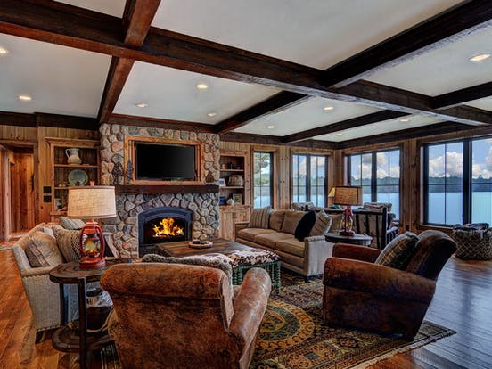 Dark and rustic Sayner, WI living space with large stone fireplace
