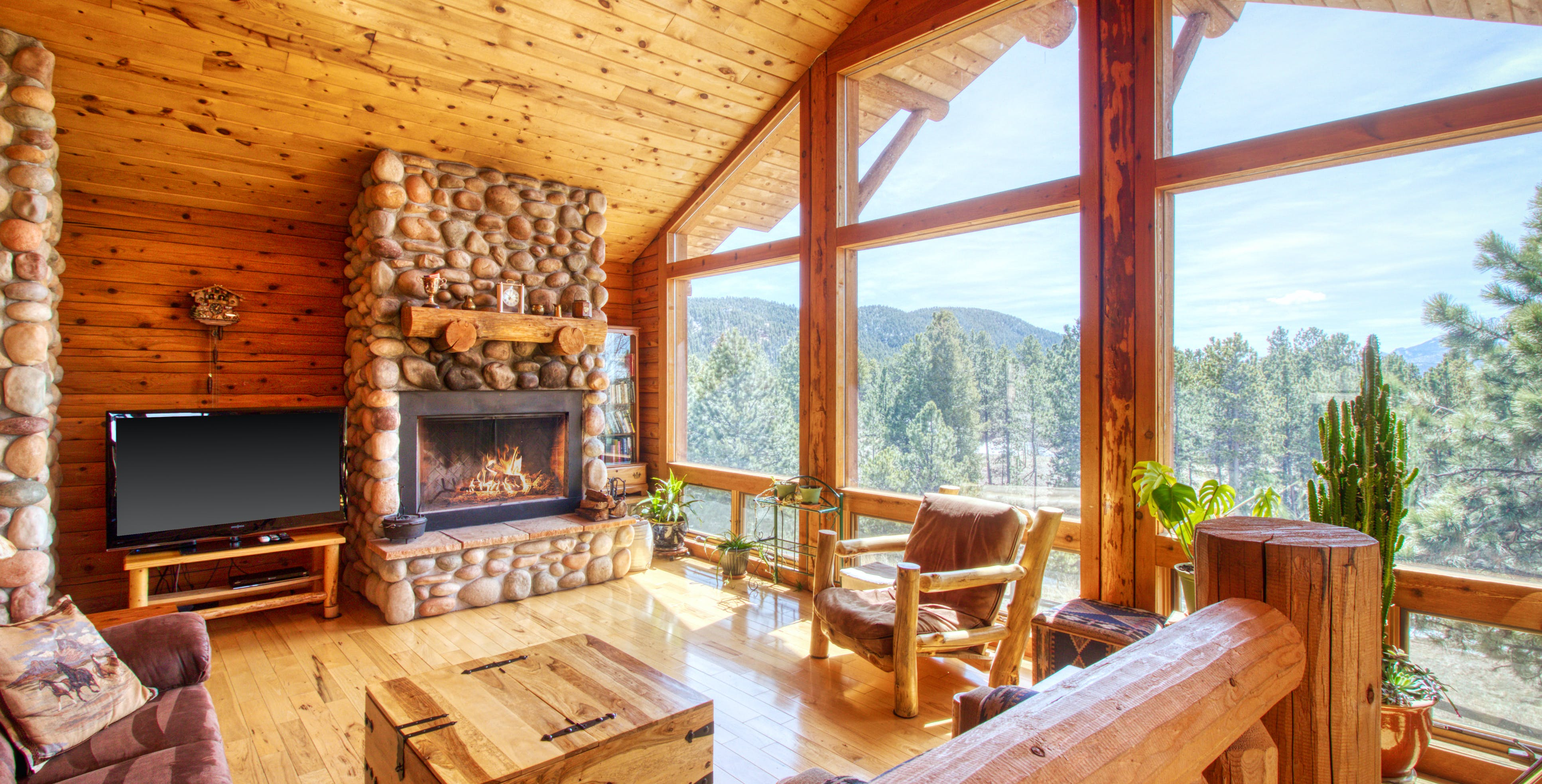 gorgeous wood accented interior of cabin with large fireplace and huge windows in woodland park, co