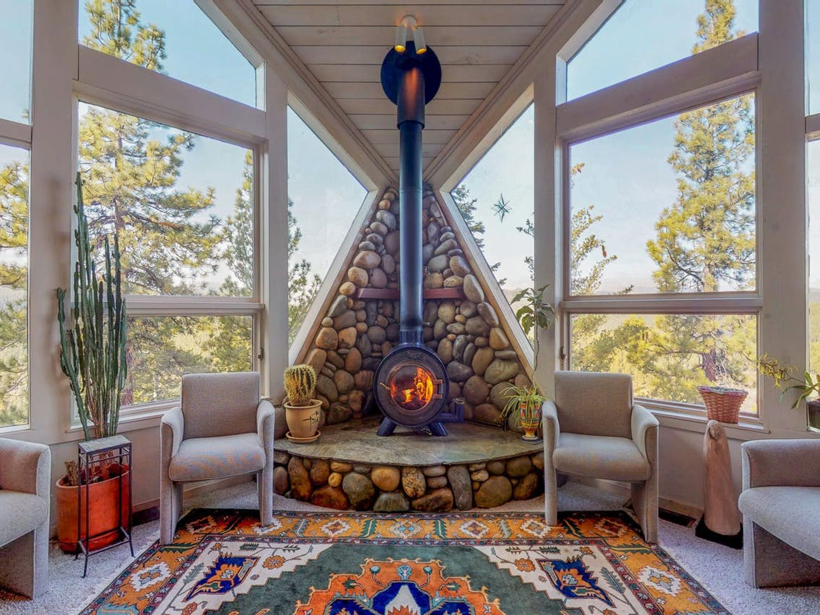 Beautifully decorated living area of Truckee cabin with stone fireplace, cactus, and a bold rug overlooking with large picturesque windows