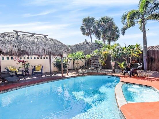 Tropical decor surrounds outdoor pool in Cocoa Beach