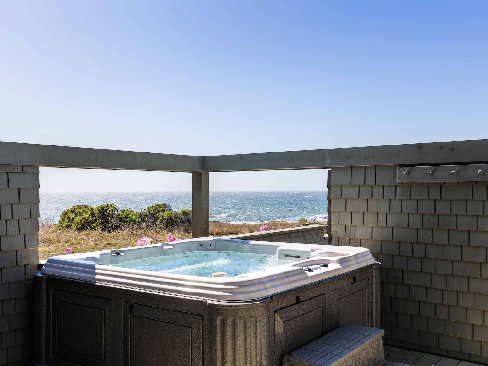 Vacation rental back patio with private hot tub and views of the ocean