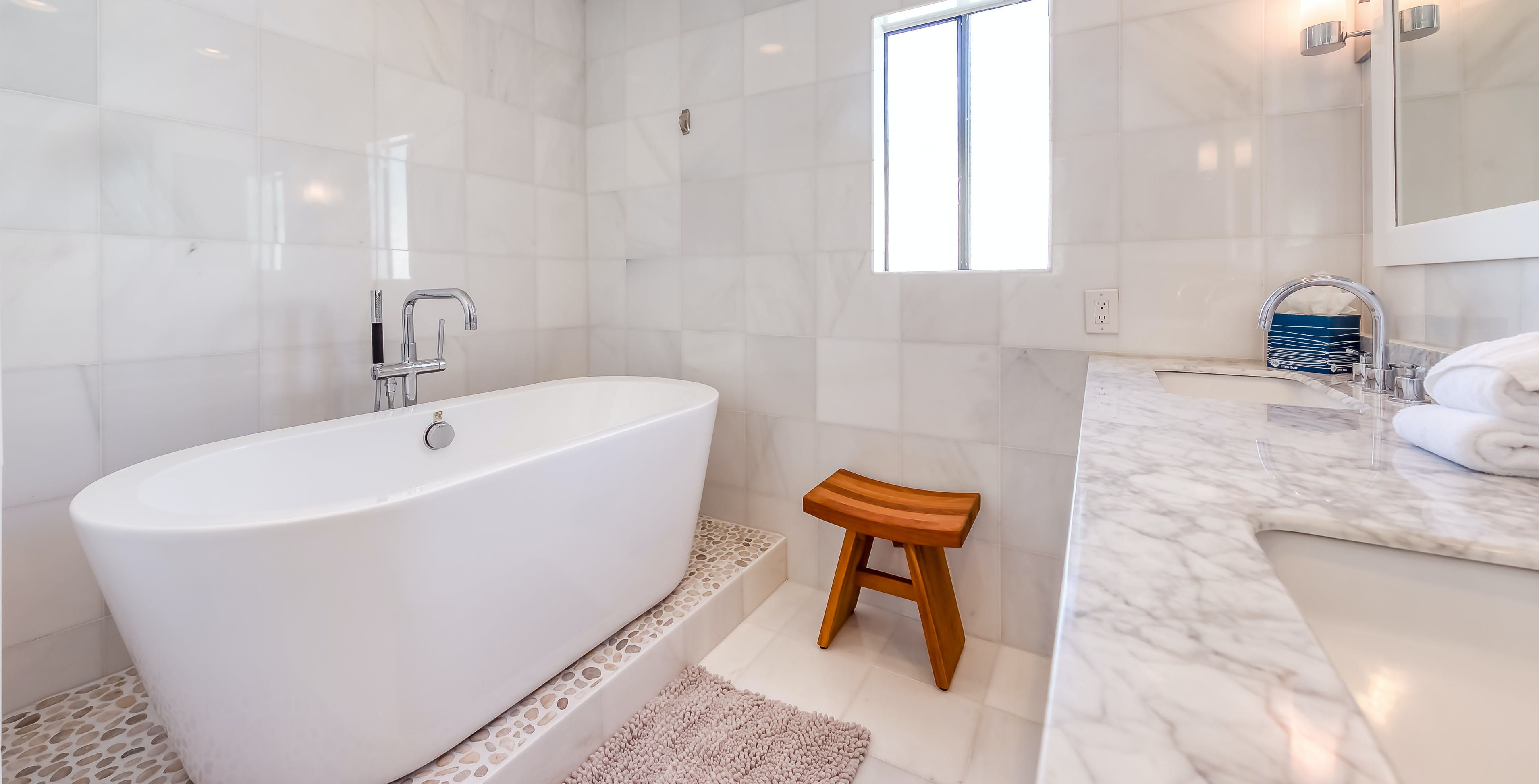 Inside a modern style bathroom of a vacation home with a freestanding bathtub in Palm Springs, CA.
