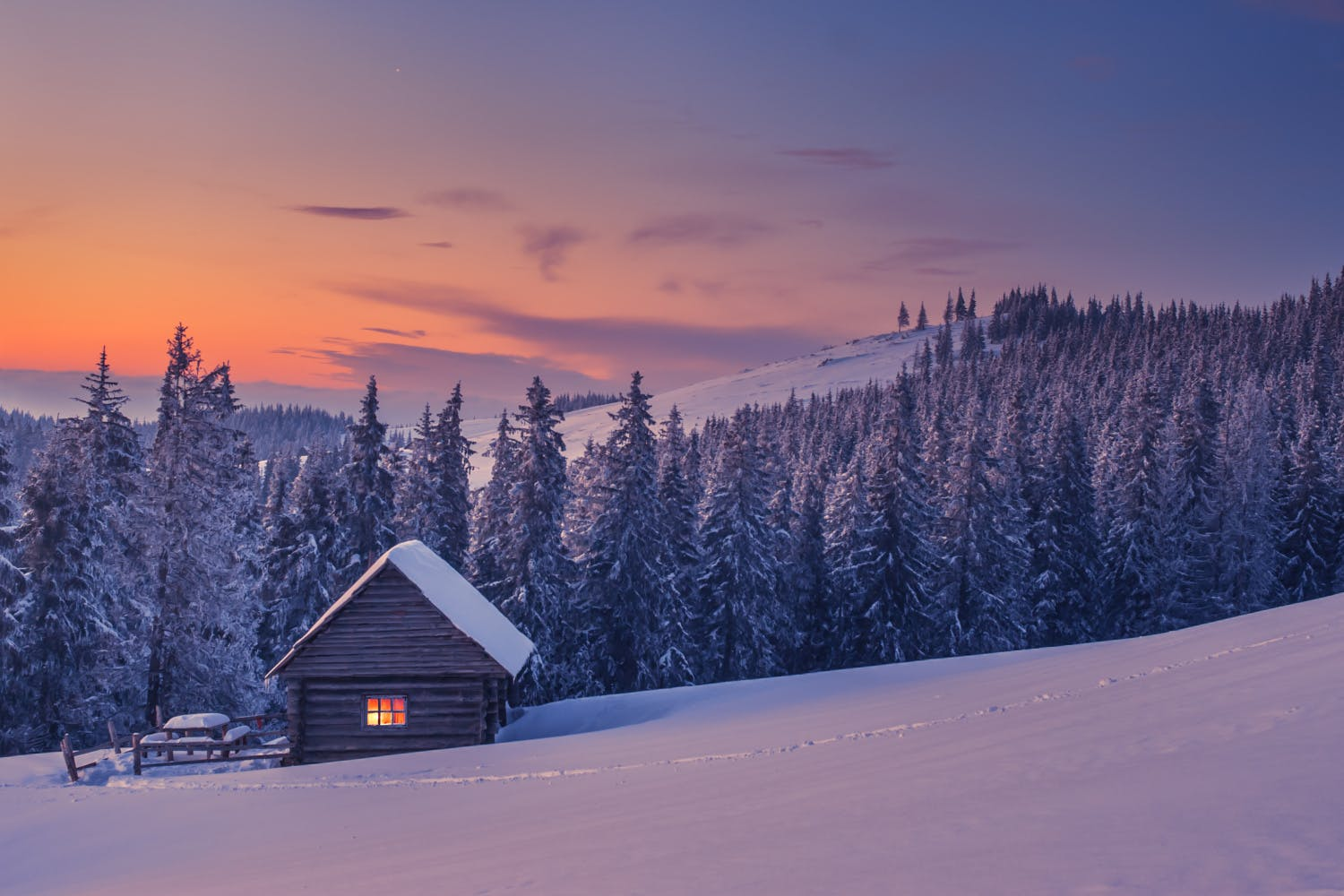 a cabin in the woods surrounded by snow on a winter evening