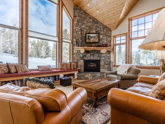 big sky, mt vacation home with large stone fireplace and floor-to-ceiling windows