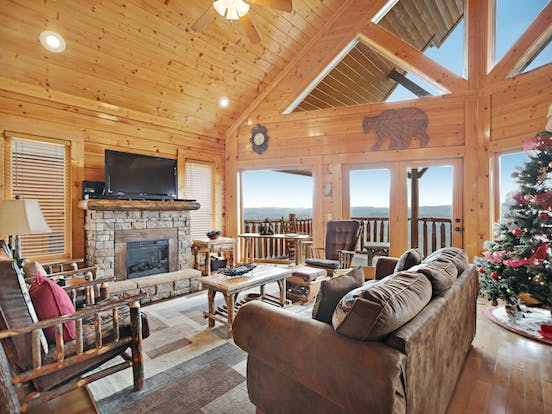 large living space with fireplace and large windows overlooking the smoky mountains