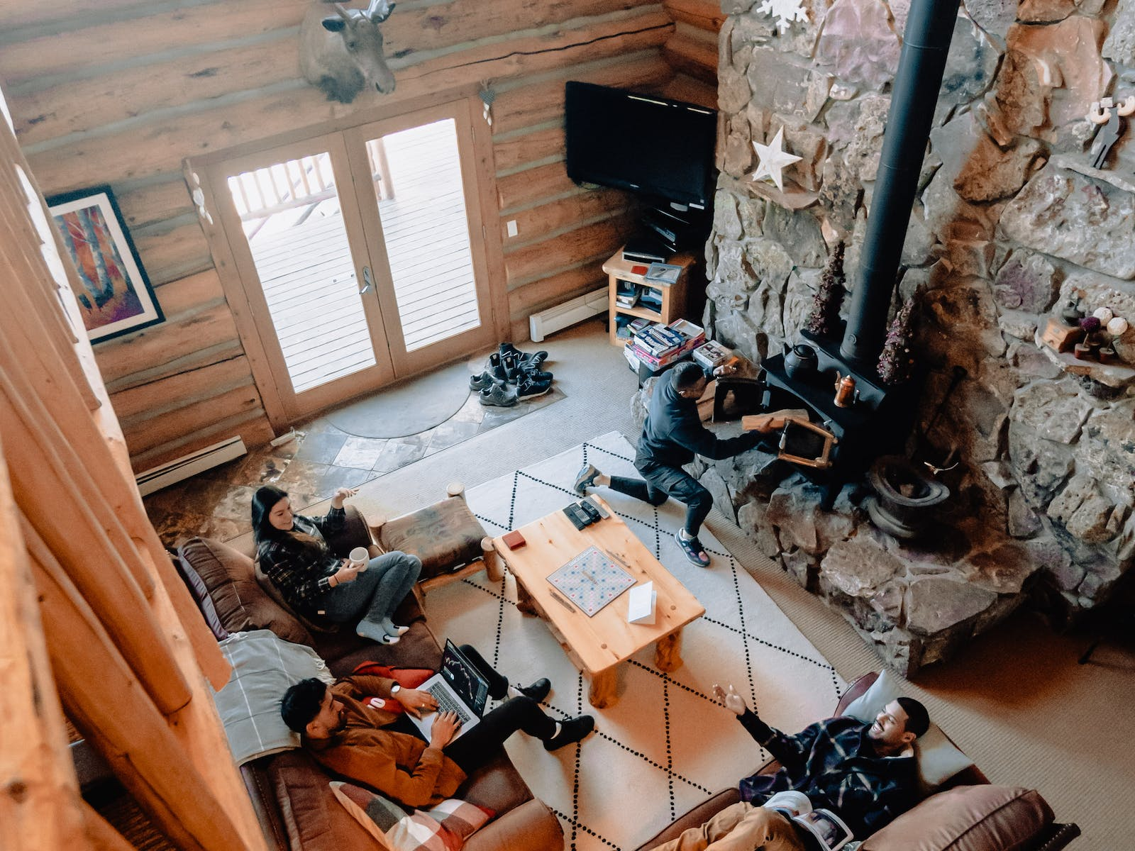 group of four friends hang out in living area of vacation cabin