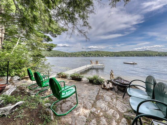 Outdoor chairs overlook boat dock on Brant Lake