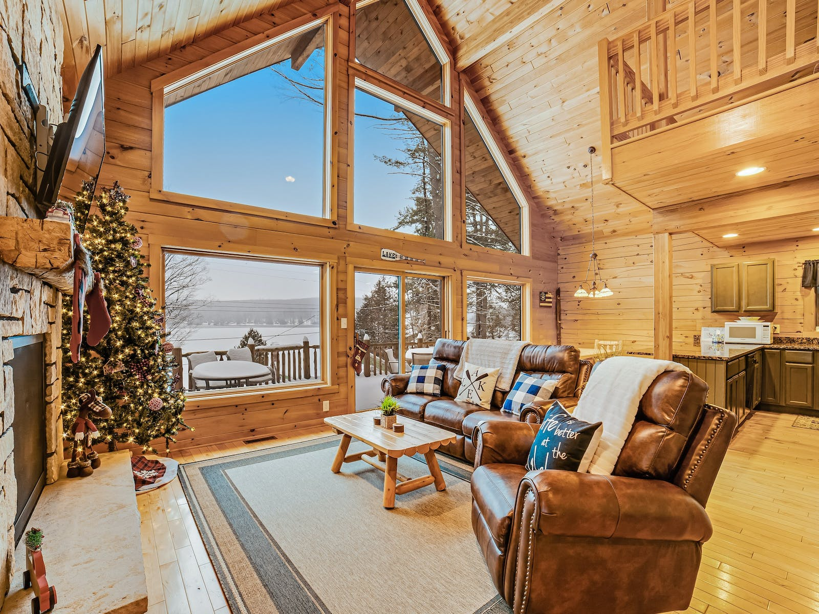 cozy living room with christmas tree and stone fireplace of Shroon Lake, NY cabin