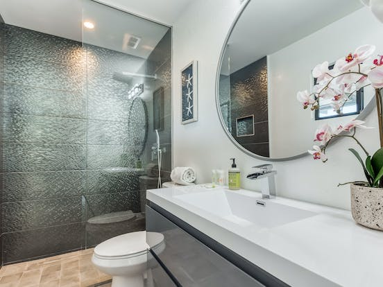 large tiled shower with glass door in vacation home bathroom in palm springs