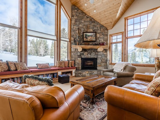 large stone fireplace and comfy leather couches inside a big sky, mt vacation home