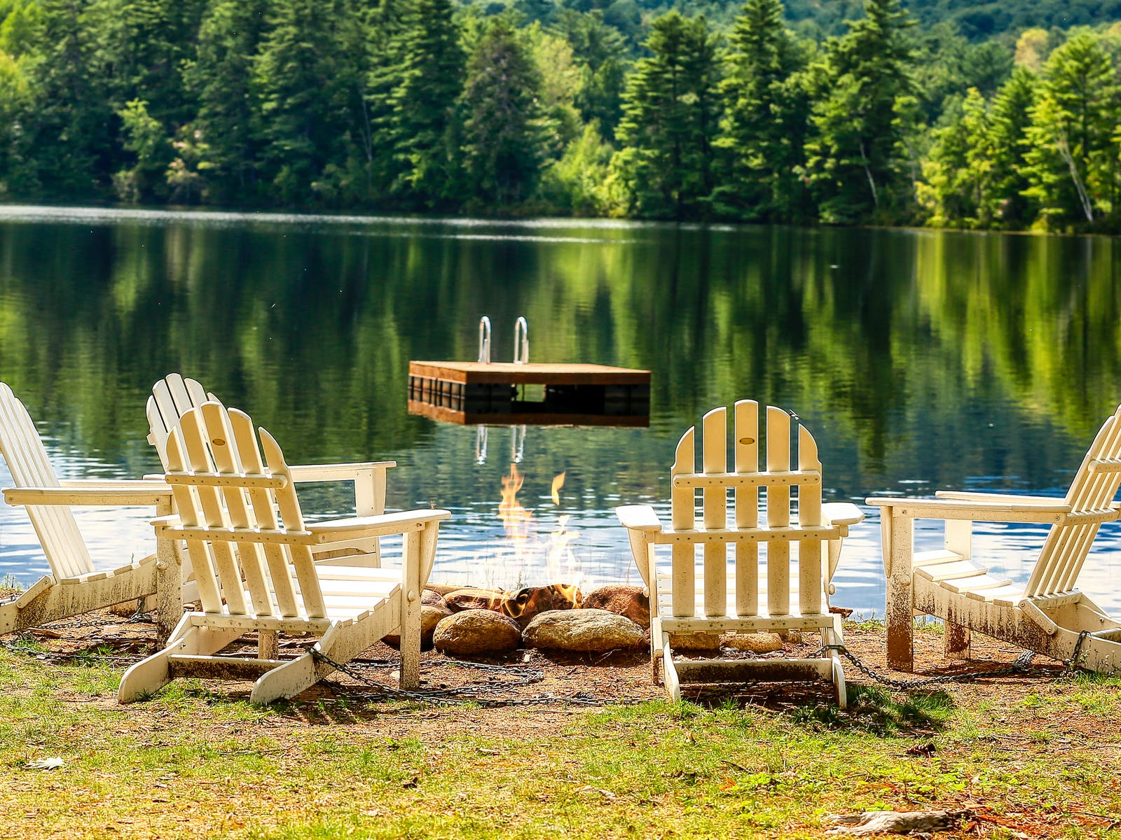 Adirondack chairs surround a fire with a floating dock in NH lake