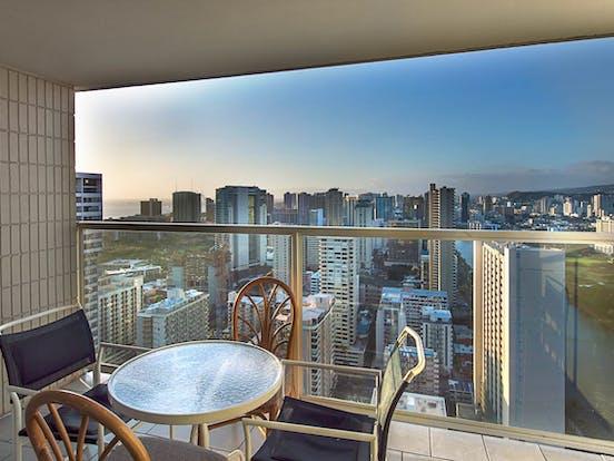 Condo rental balcony in Honolulu overlooking the skyline