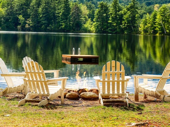 Adirondack chairs surround a fire with a floating dock in the lake beyond