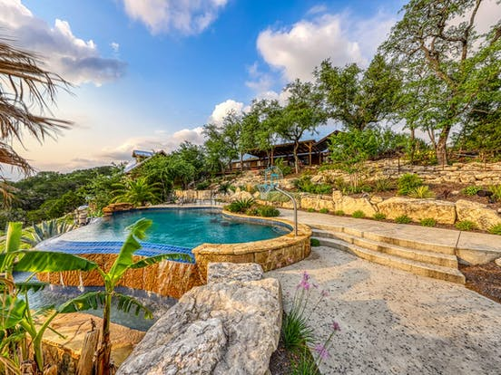 Lake Travis vacation rental with outdoor pool surrounded by tropical forest