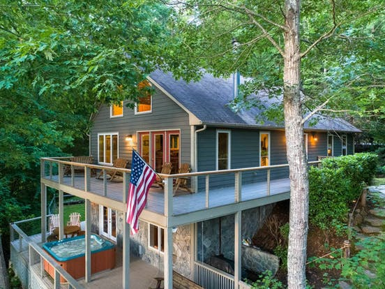 vacation home with outdoor hot tub and american flag hanging off second floor balcony