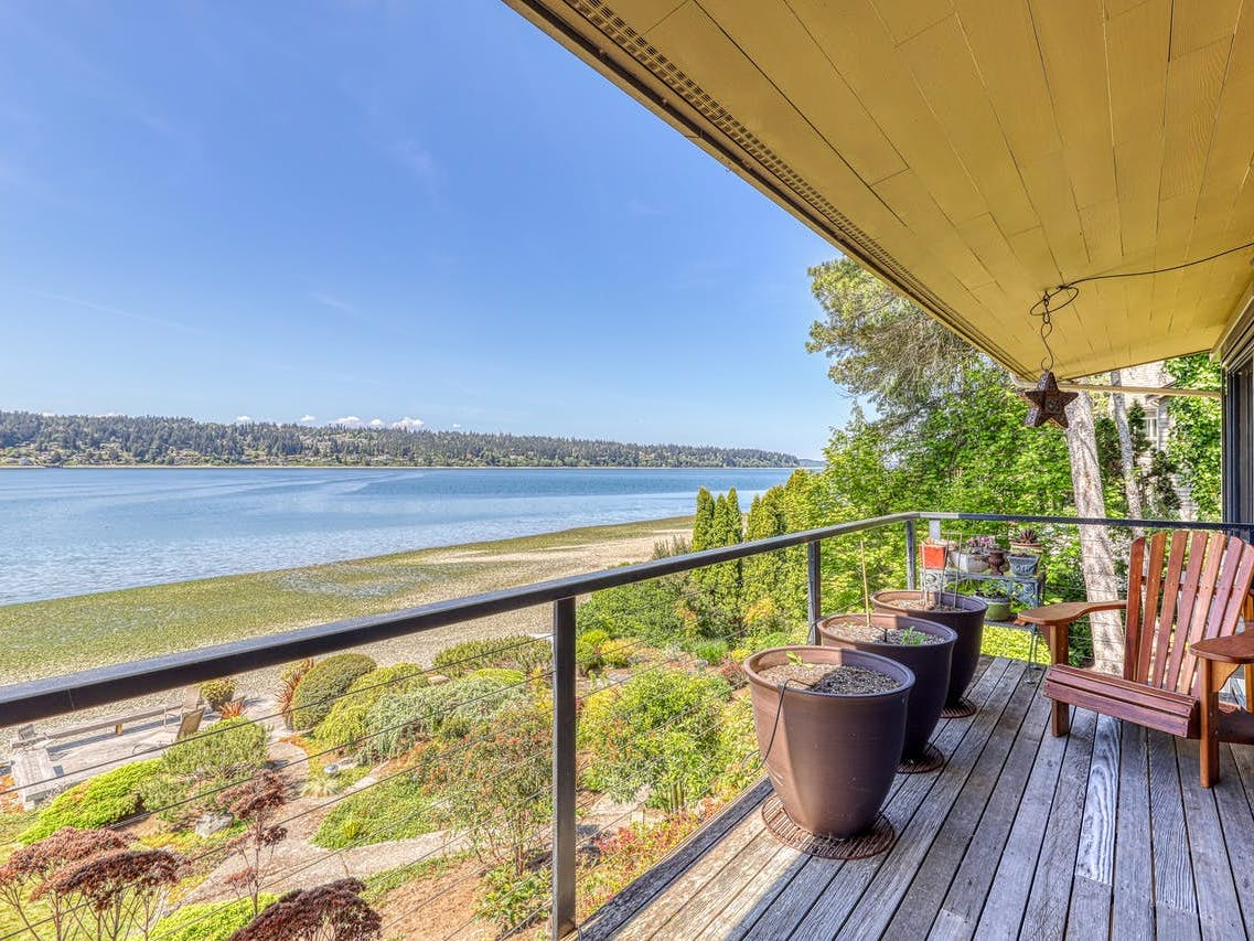 Seattle waterfront vacation rental deck with plants and chairs for relaxing