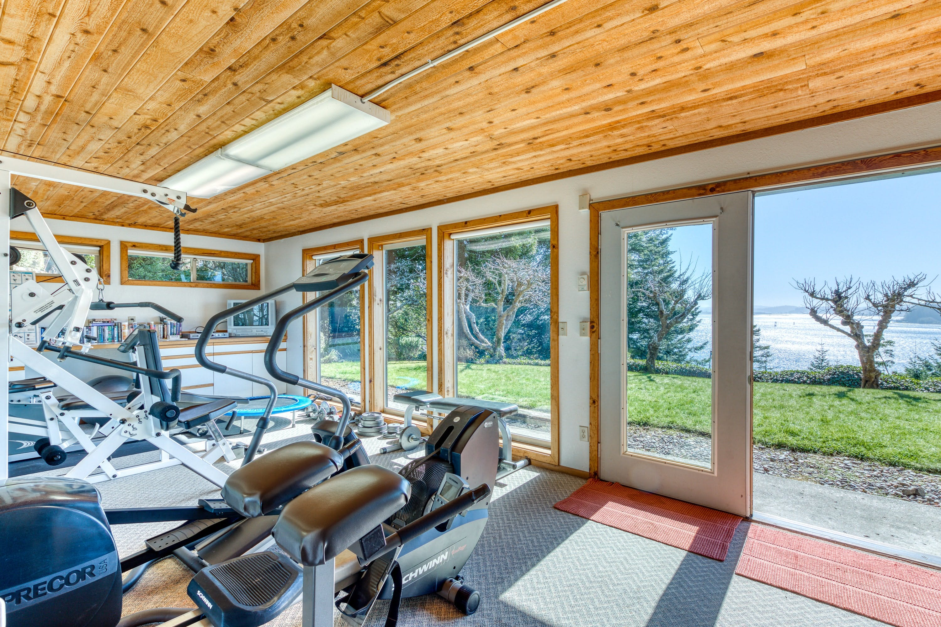home gym with gorgeous views inside vacation rental in North Bend, Oregon