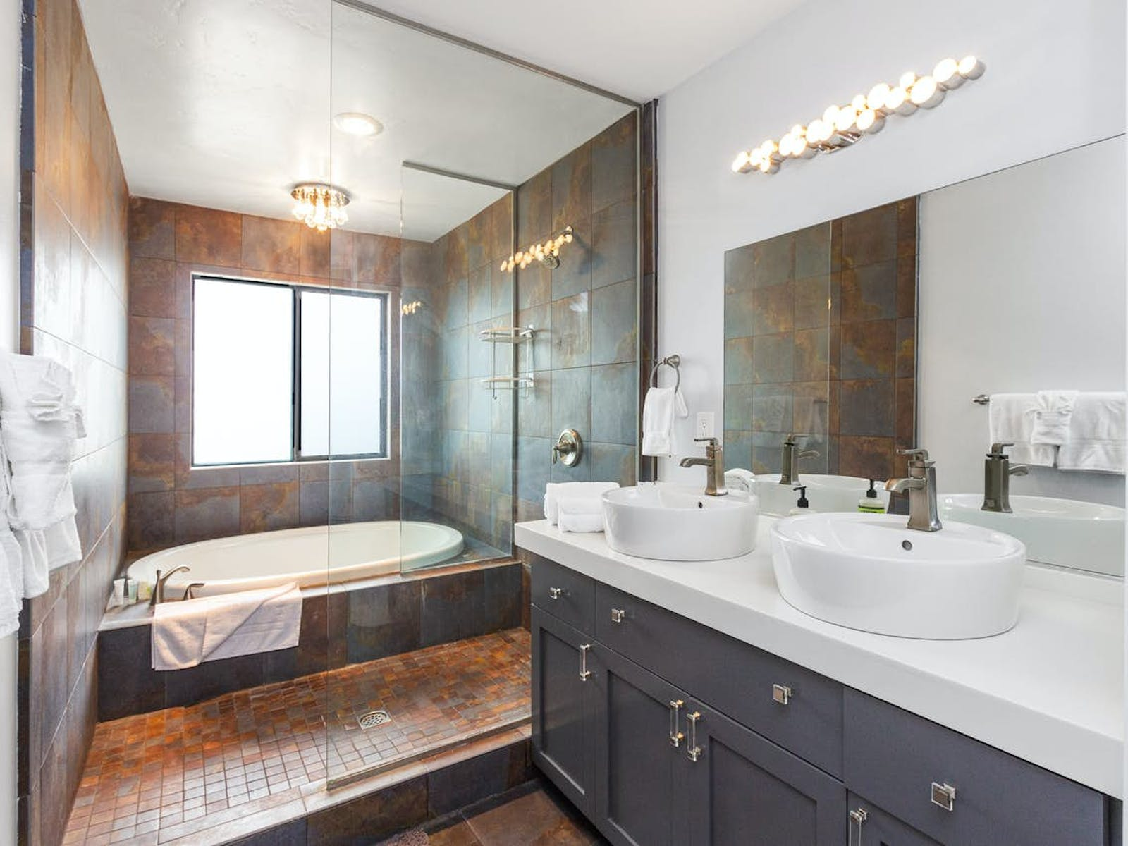 bathroom modeled after a European wet room, with a fully tiled, open layout for the shower and sleekly sunken tub