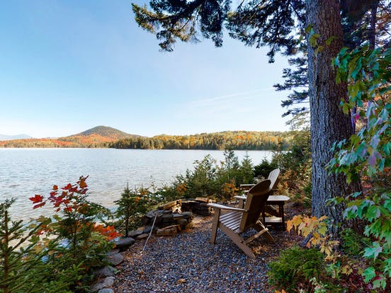 adirondack chairs perched at the water's edge in moosehead lake