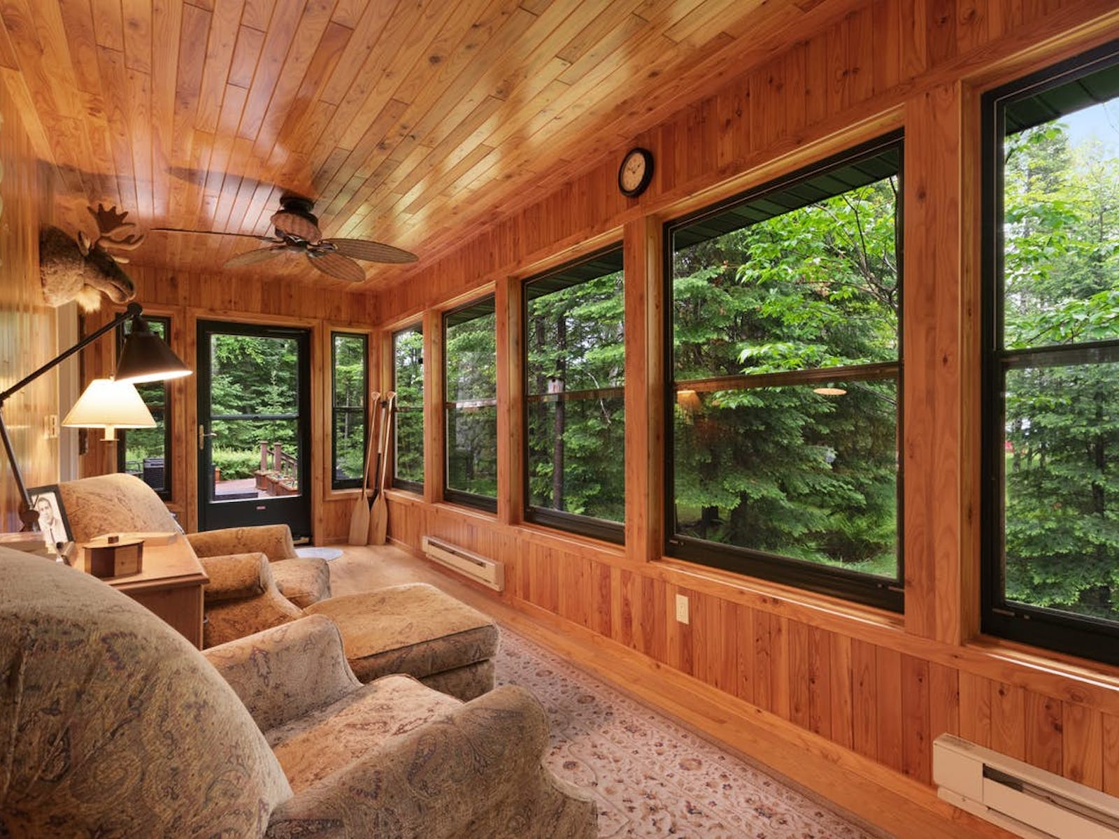 interior of vacation cabin in Rhineland, WI with comfy couches, lots of windows and forest views