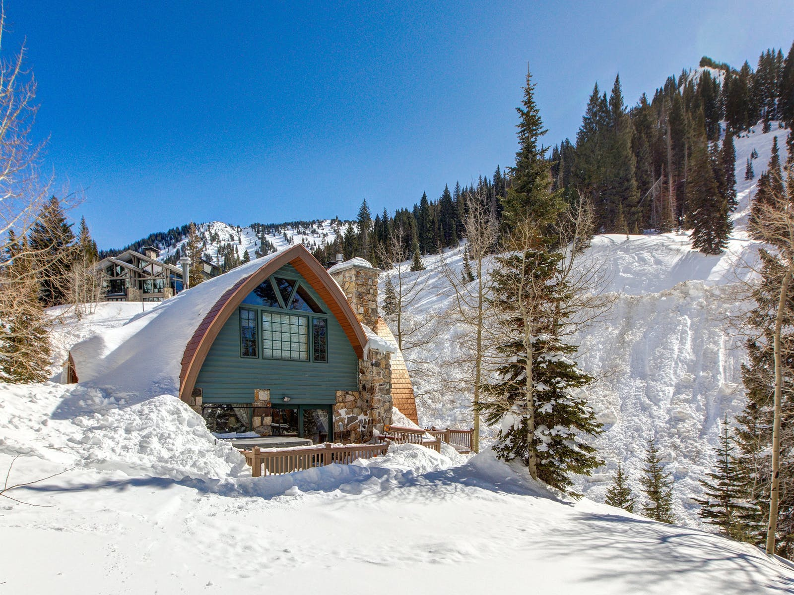 A green chalet rental covered in snow on a mountain side in Alta, UT.