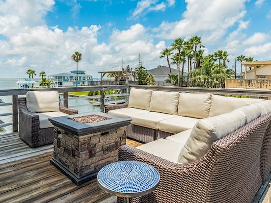 Vacation rental balcony with couch and fire pit
