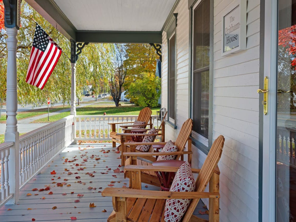 moosehead lake vacation home with covered front porch with adirondack chairs and an american flag