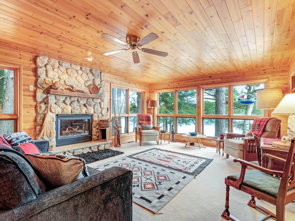 Interior of Eagle River, WI cabin with ample seating, a stone fireplace, and adorable accents