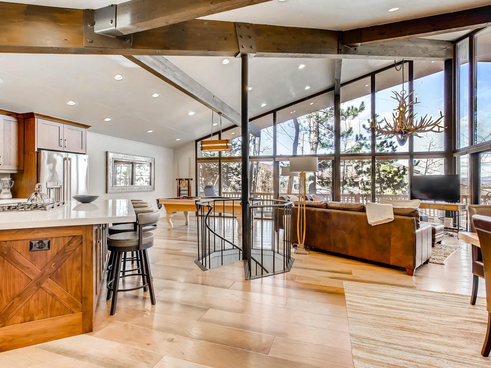 large open living space with spiral stairs and floor-to-ceiling windows of park city condo