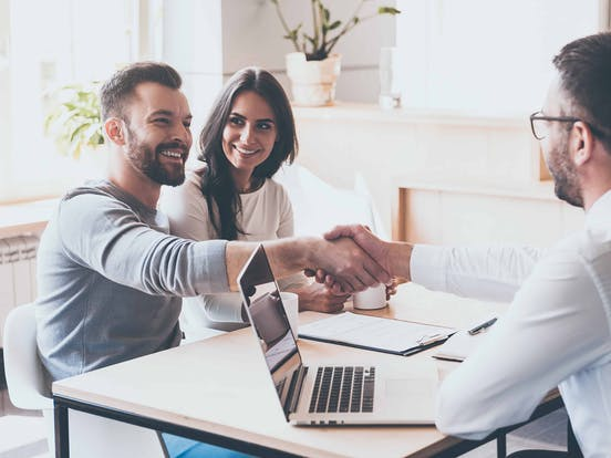 Vacation home buyer shaking hands with their real estate agent