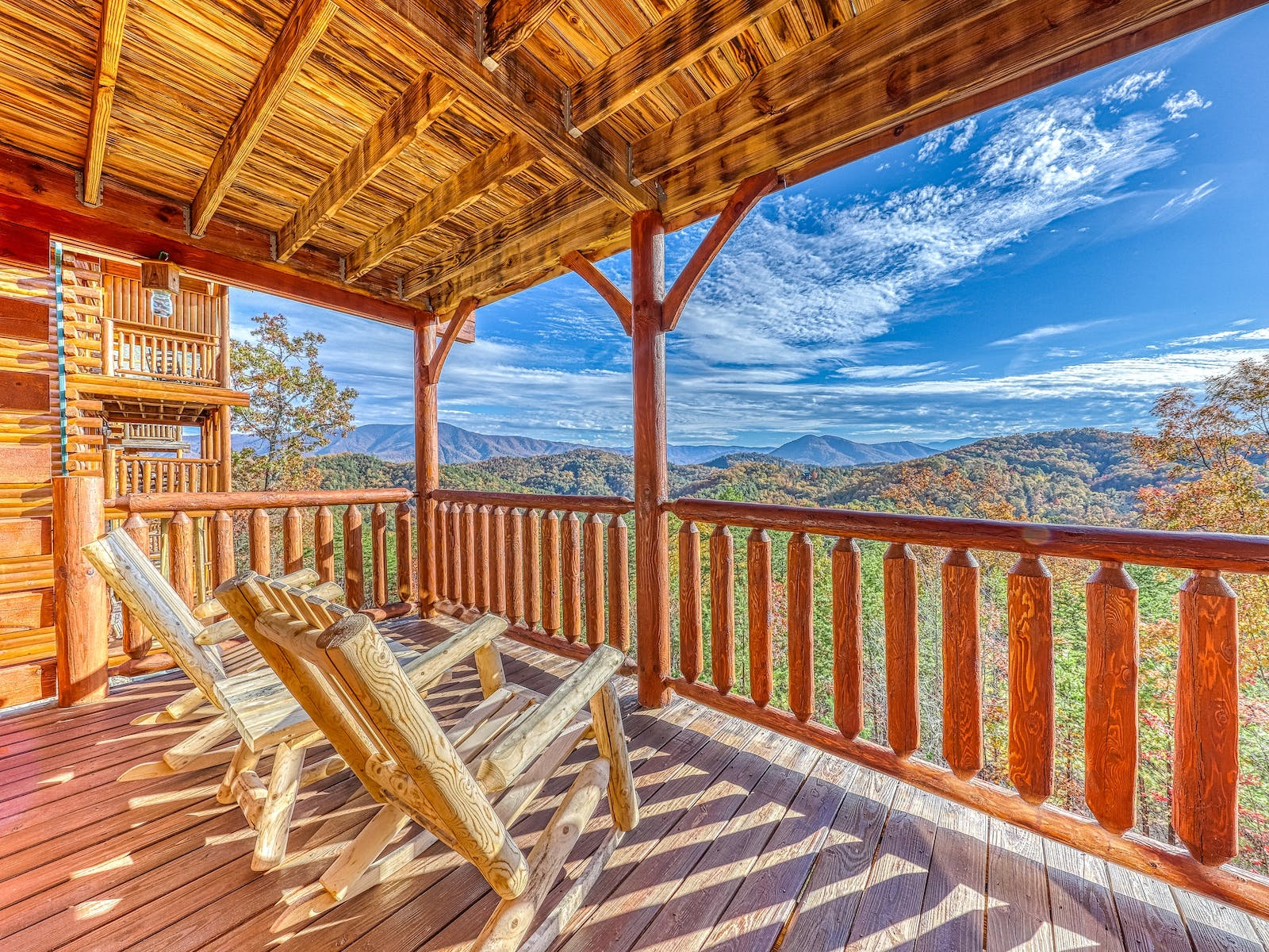 The balcony of a cabin rental with adirondack chairs with a Smoky Mountain view in Pigeon Forge, TN.