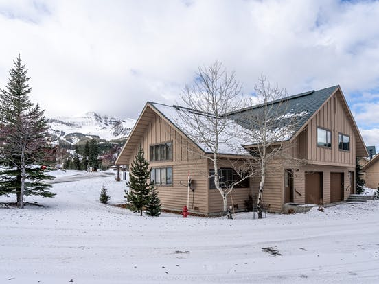 vacation rental in big sky surrounded by pine trees and snow