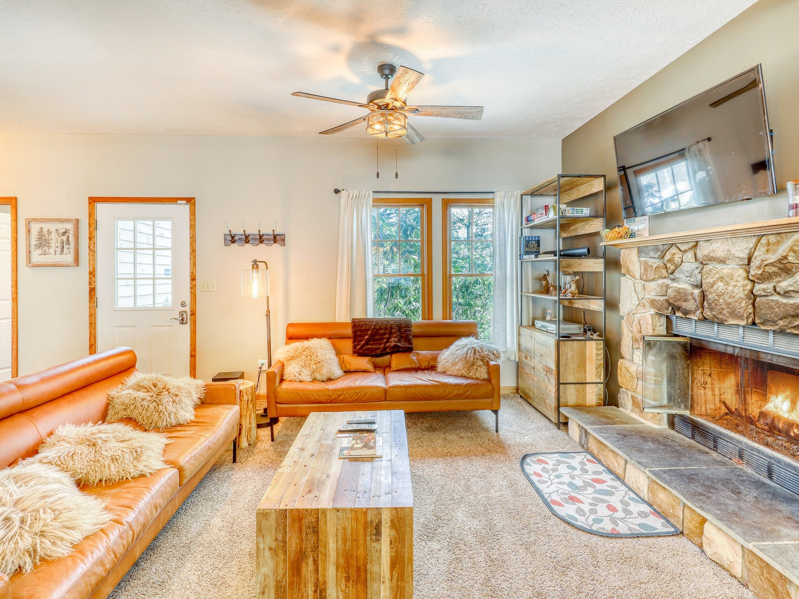 cozy living room with leather couches, a large stone fireplace and fluffy white throw pillows in tannersville, pa vacation home