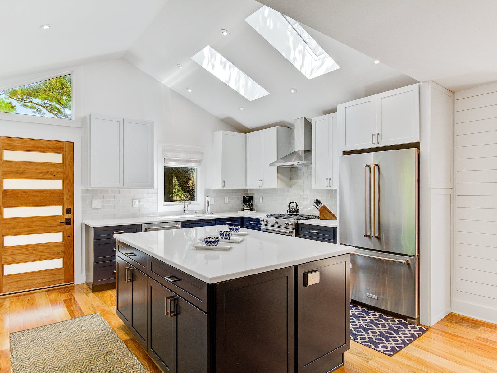 contemporary kitchen with stainless steel appliances, ample storage, skylights, and a custom island