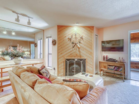 Angel Fire, NM vacation rental with wood paneled fireplace with a dream catcher mounted above