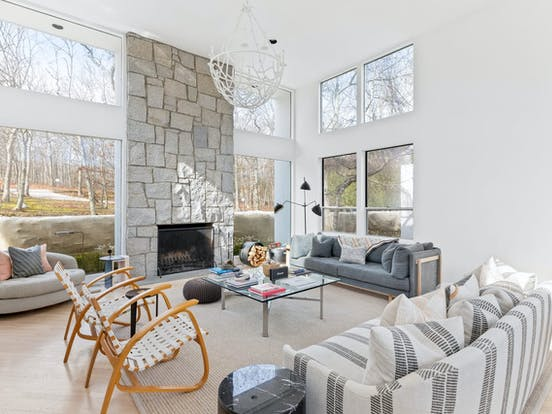 neutral-hued living space with stone fireplace in East Hampton, NY