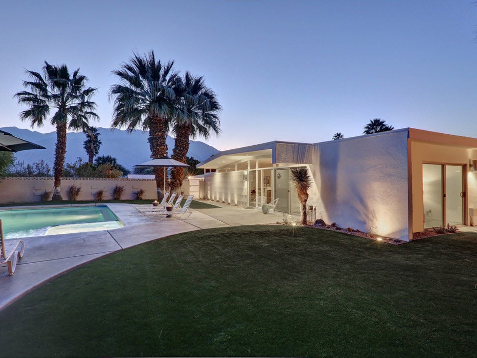 A vacation rental with an outdoor pool and palm trees with modern architecture in Palm Springs, CA.